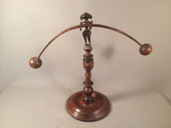 A folk art balancing toy on a reused Georgian stand. 19th century.